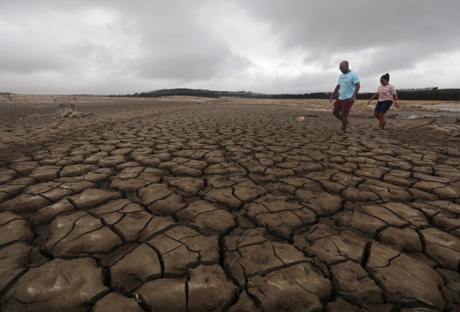 A family negotiates their way through caked mud around a dried up section of the Theewaterskloof dam near Cape Town.