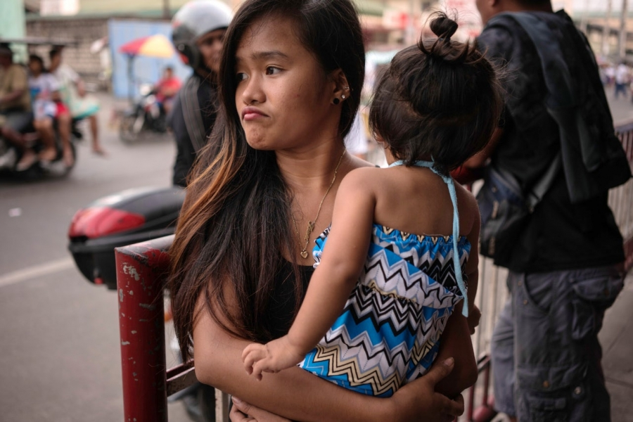 Jazmine Durana walks with her daughter Hazel in Navotas City, north of Manila, Philippines. Durana's partner was killed a year ago by masked men.