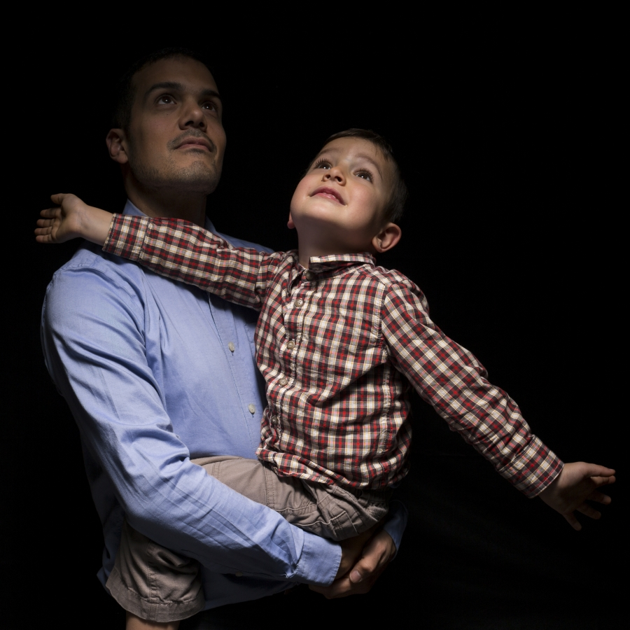 Man holding toddler whose arms are outstretched, against balck background