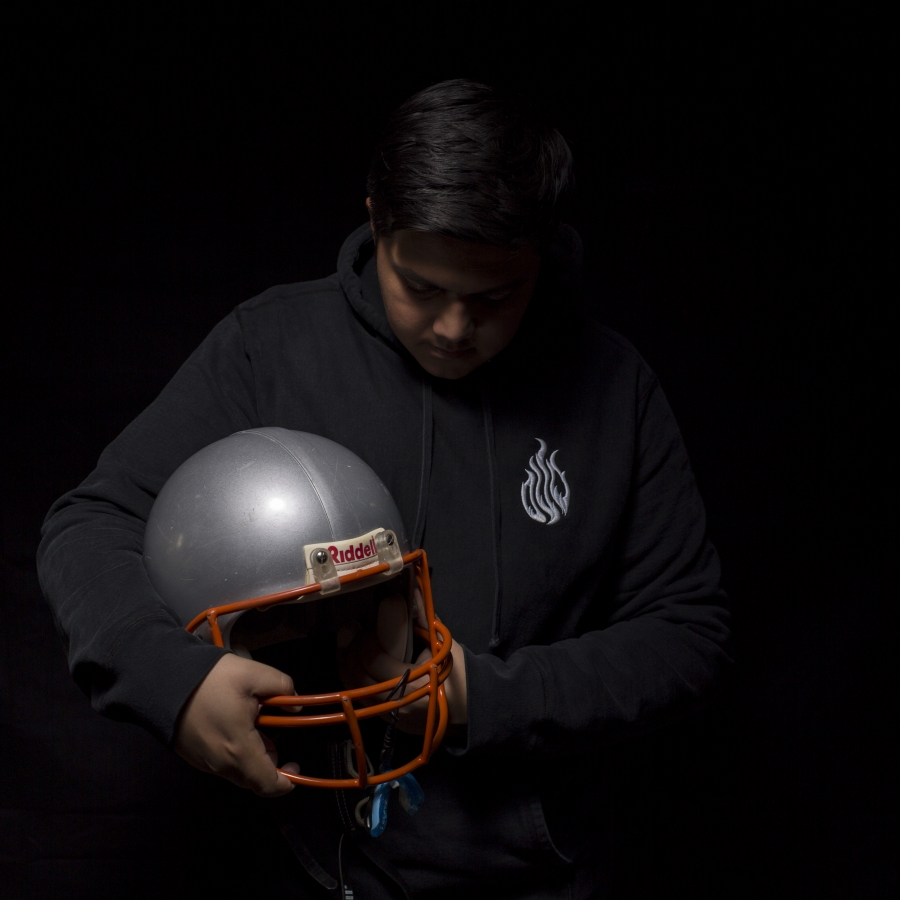 Young man against black bakcground, holding football helmet