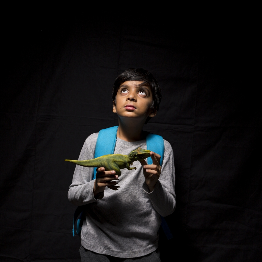 Boy holding toy dinosaur looking up, against black background