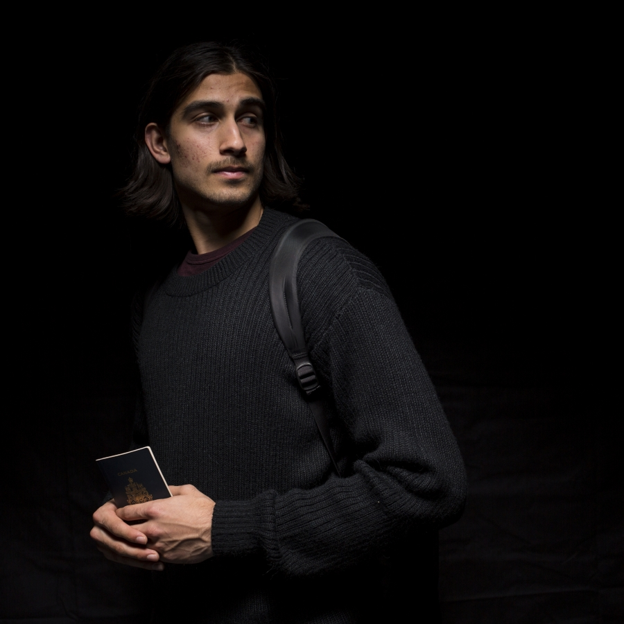 Young man with backpack and tablet, against a black background