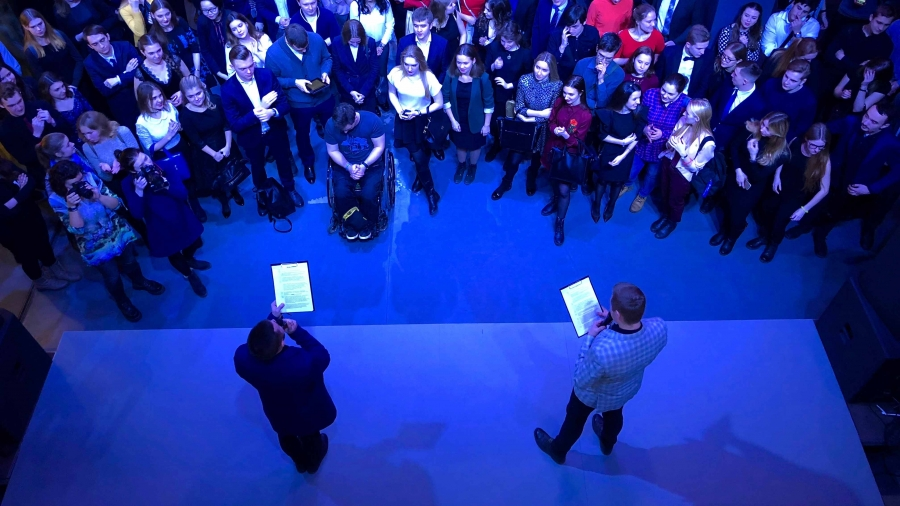 The view overhead of a crowd gathered around a stage while two men read from clipboards. The room is bathed in blue light.