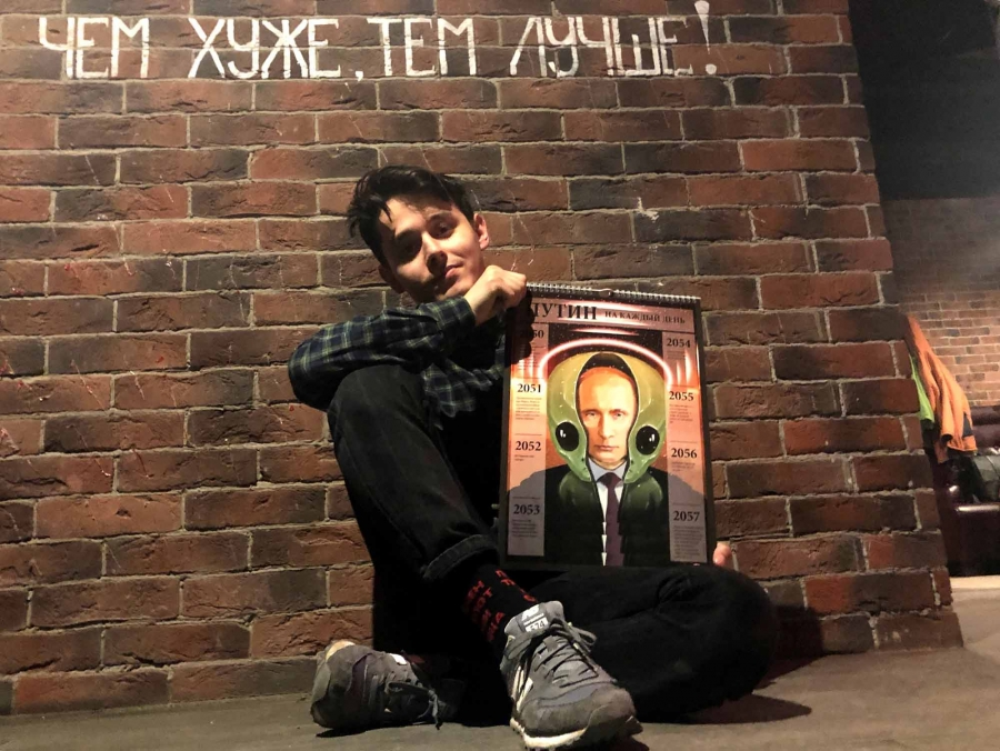 A young man poses with an oversized calendar against a brick wall. The cover of the calendar has an illustration of Vladimir Putin wearing an alien-shaped helmet.
