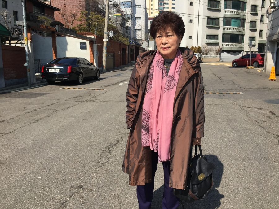 Portrait of Sue Kinsler, a Christian missionary who helps North Korean disabilities, wearing a brown jacket and pink scarf.