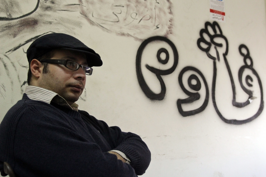 "Ahmed Maher photographed in January 2013, in the headquarters of the April 6 Movement. The writing on the wall reads ""resist."""