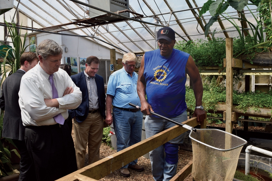 Will Allen demonstrates his aquaculture system for Agriculture Secretary Tom Vilsack (left) in 2015.