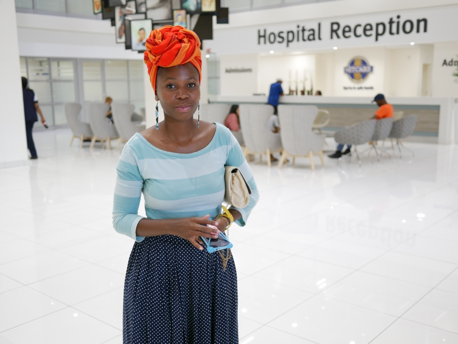 Somila Makangume, a Cape Town resident, in an orange head wrap and blue striped shirt, at Christiaan Barnard Hospital.
