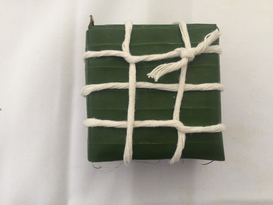 Packet of food in leaf wrapping, with string around it