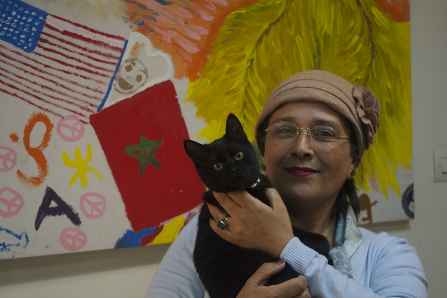 Jamila Bargach and he cute cat in front of a mural