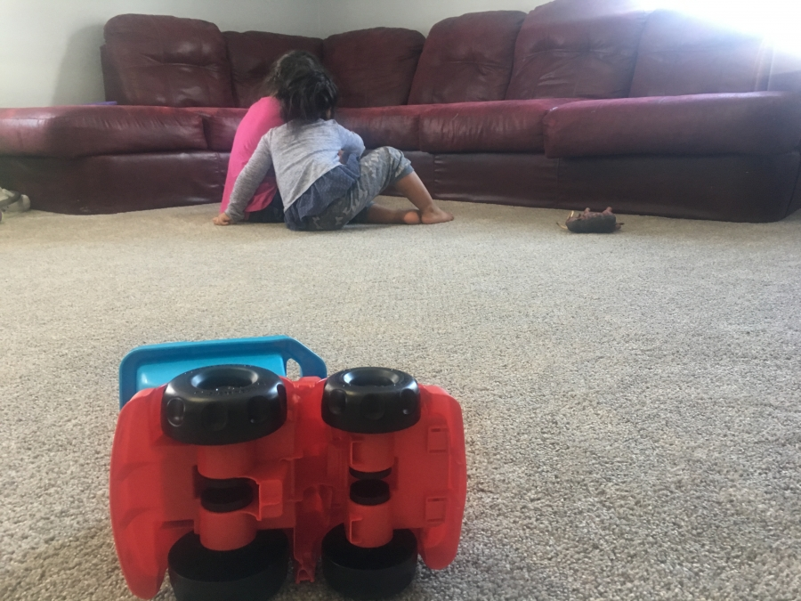 Two girls playing next to sofa with backs to camera, toy truck in the foreground
