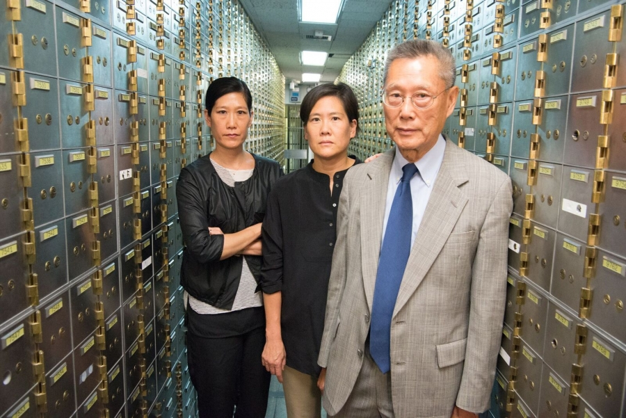 Two women and an older man stand in a hallway of deposit boxes.