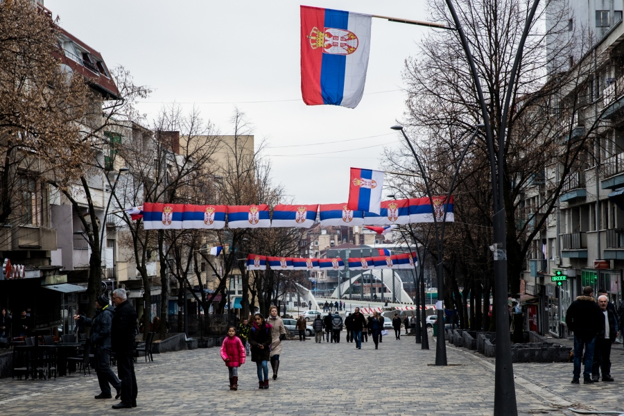 Serbian flags line a pedestrian-friendly road in North Mitrovica, a Serb-majority area in northern Kosovo. The city is split along ethnic lines, divided by the Ibar River.