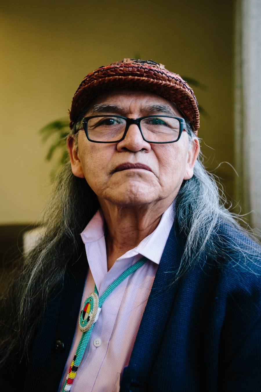 An older Indigenous man wearing hat looks towards the camera.