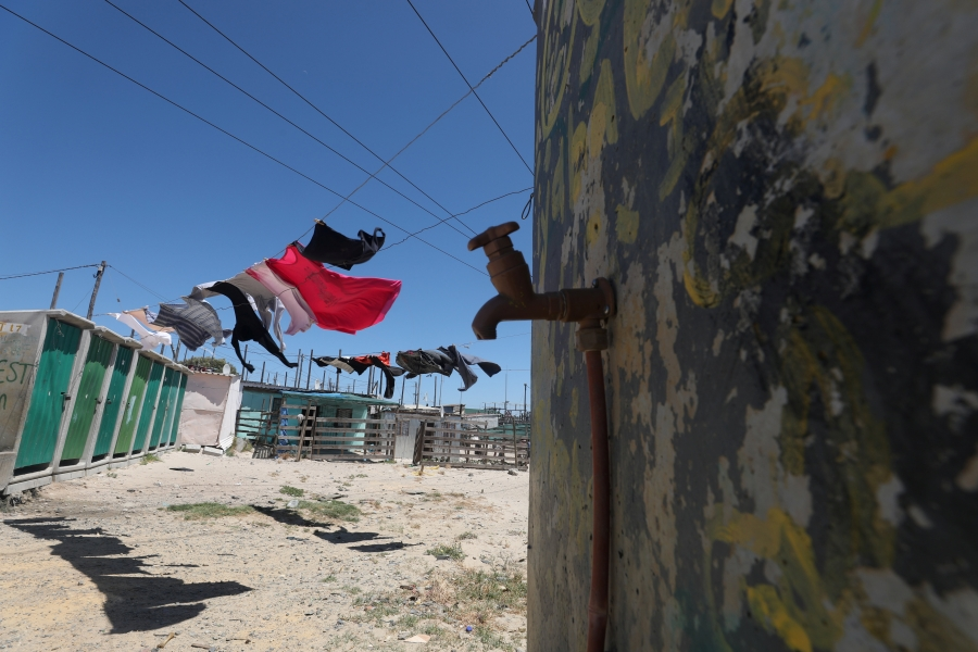 Clothing hangs above a communal tap in Khayelitsha township, near Cape Town,