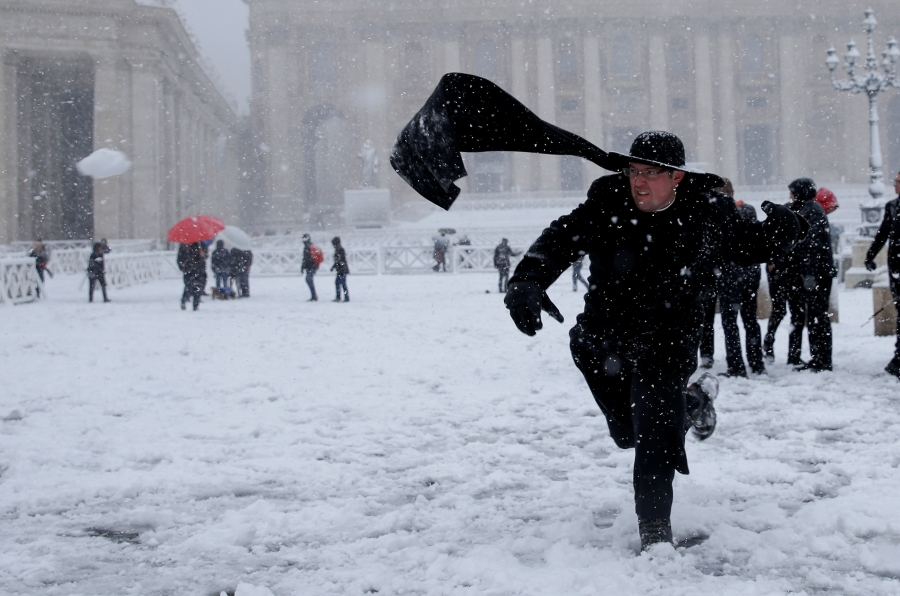A priest plays with snow during a heavy snowfall in Saint Peter's Square at the Vatican on February 26.