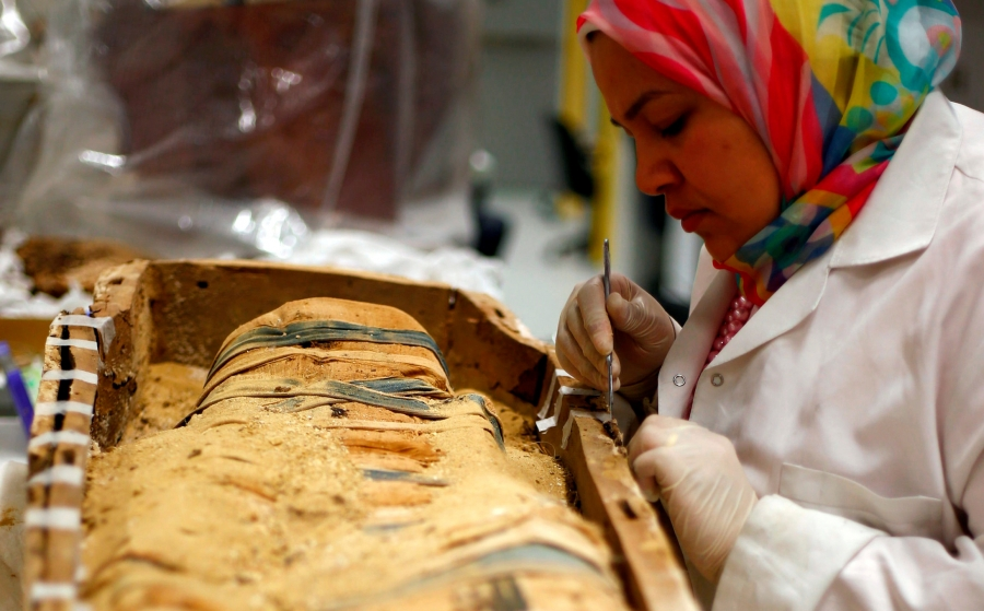 An Egyptian archaeological technician renovates one of the mummies which belonged to The Golden King Tutankhamun