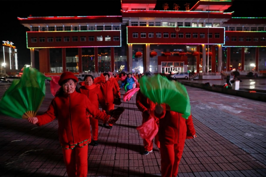 Women participate in a group dance exercise close to the Yalu River
