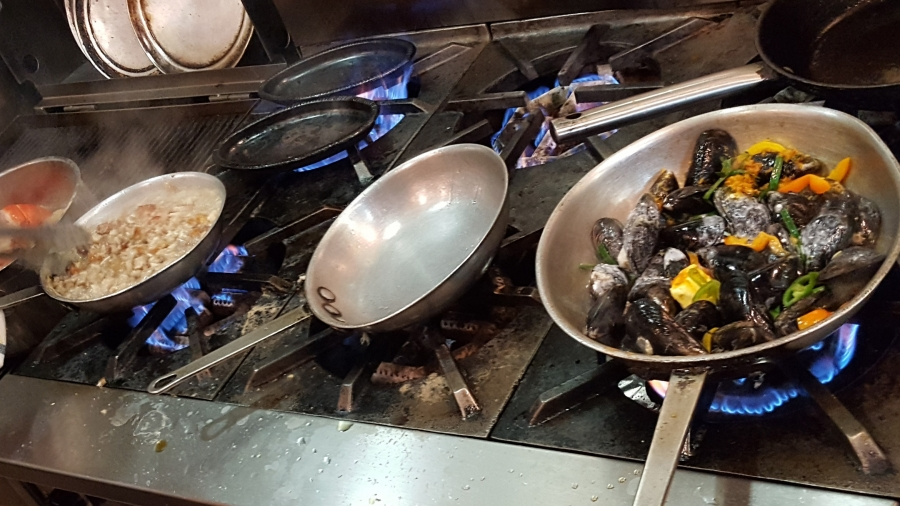 Three burners on commercial stove, cooking food