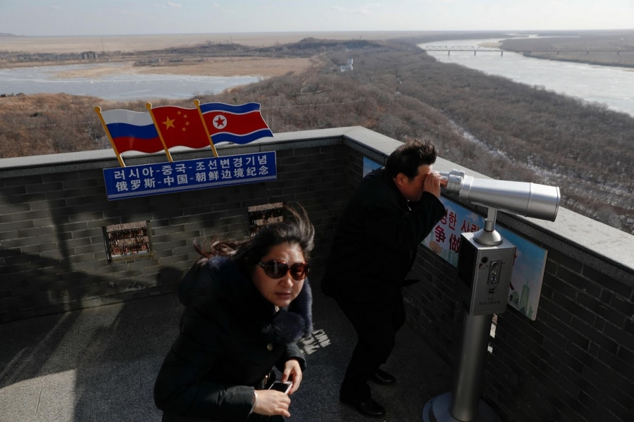 A tourist uses binoculars to look across to North Korea from a tower built on the Chinese side