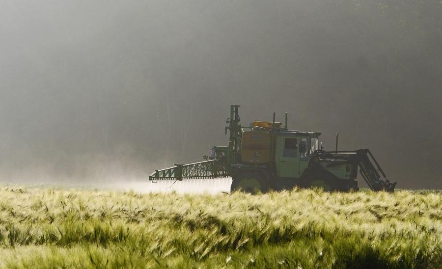 Farm tractor spraying crops.