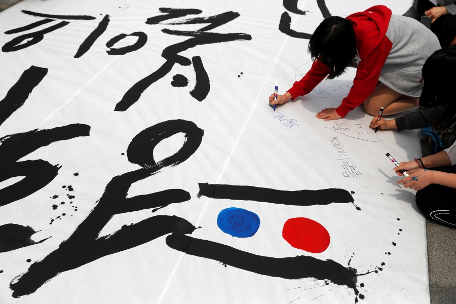 People write goodwill messages during a pro-unification rally