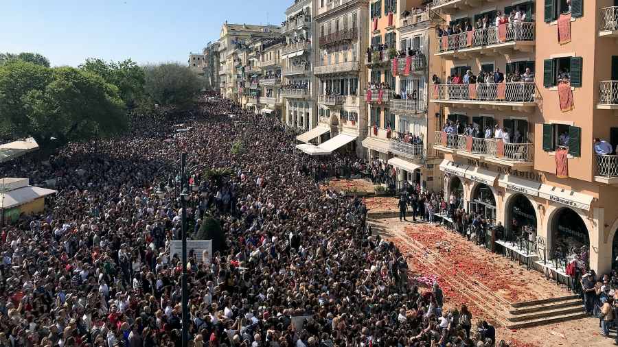 Crowds of people stand in the street while others hang out of windows. Below the windows are the red shards from the clay pots falling on the pavement.