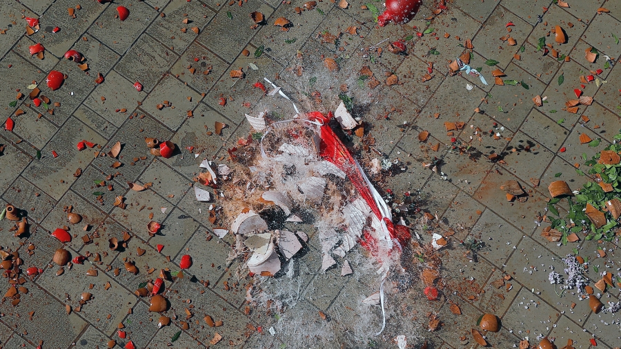Red shards of clay pot and water are mixed together on the tiled street as the jug hits the pavement and shatters.