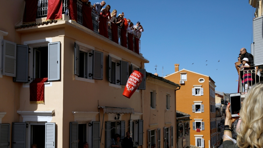 A red pot falls from a tall building as onlookers cluster on rooftops and out windows to watch.