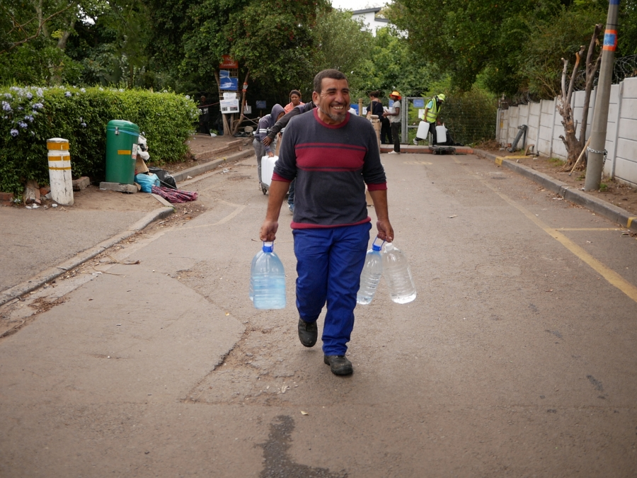 In each hand, Abbas Mustafa carries one of the 18 bottles of water he filled at a spring in Newlands, Cape Town.