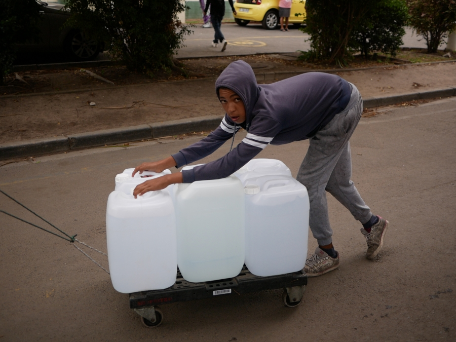 A boy pushes a trolley bulging with white water bottles uphill from the spring.