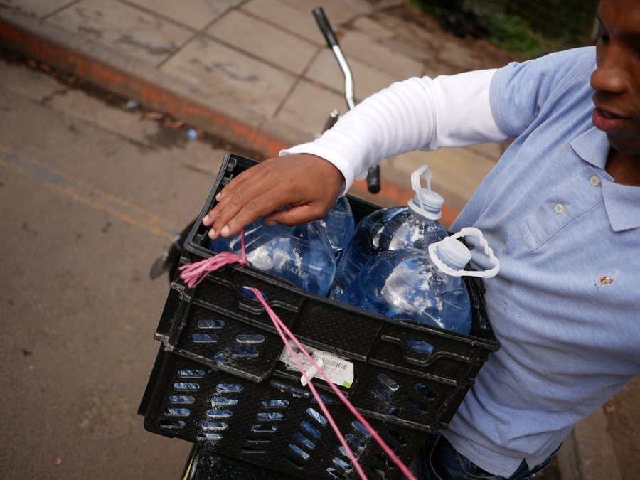 Faiek Swartz uses pink twine to tie down plastic bottles of water he filled at a spring in Newlands, Cape Town.