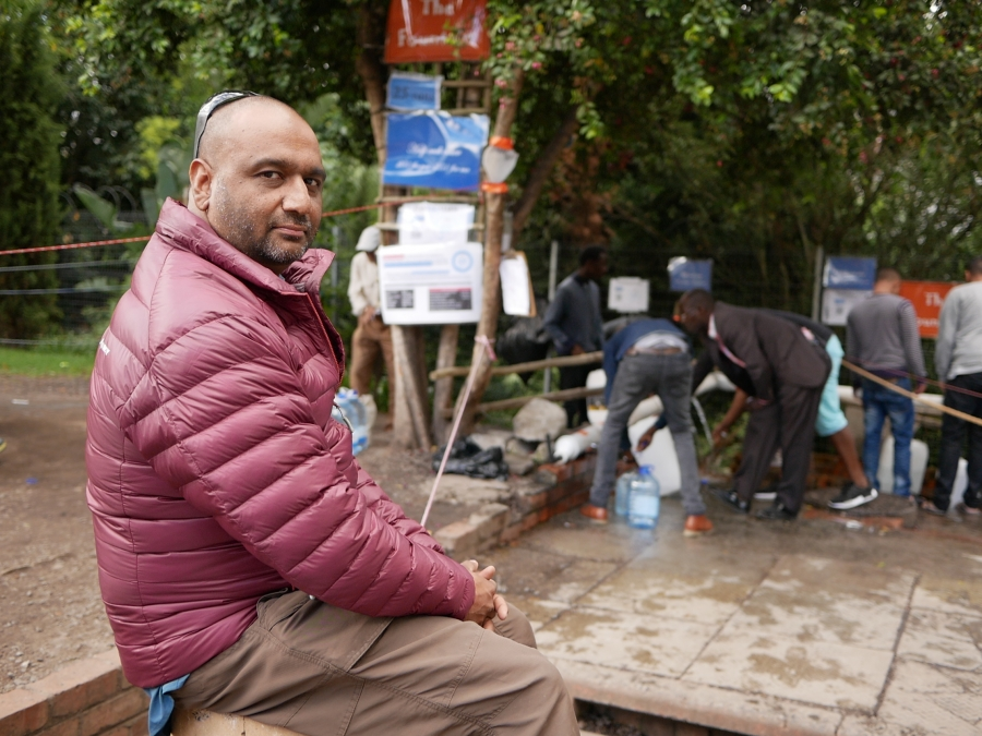 Portrait of Riyaz Rawoot, who wears a red coat as he watches people take their turns filling bottles at a spring in Newlands, Cape Town.