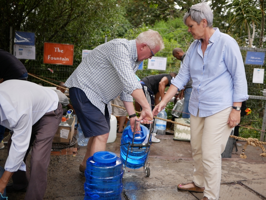 Sabine and Nils Heckscher hold jerricans to collect water at a natural spring in Newlands, Cape Town.