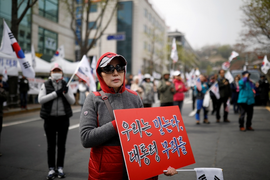 Members of a conservative civic group carry South Korean flags and placards in a street protest to support ousted President Park Geun-hye.