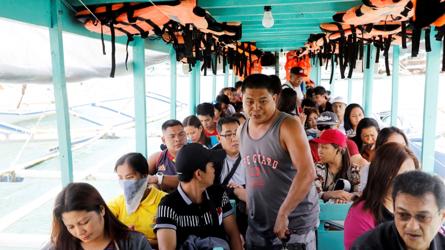 A man walks between seats of a motorboat filled with tourists. Overhead are bright orange life vests.
