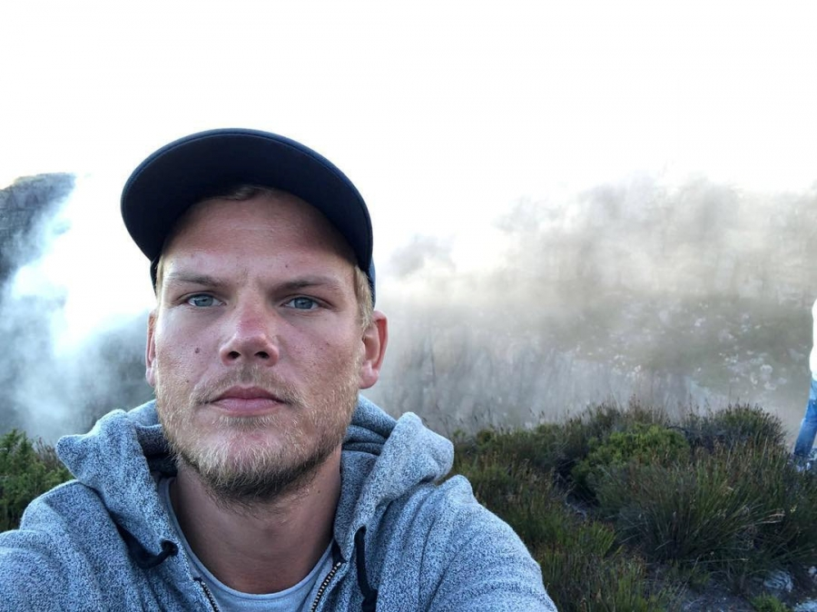 Swedish DJ Avicii wearing a hooded sweatshirt takes a selfie with Table Mountain in the background.