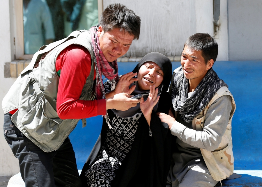 Two men hold of a greiving woman after a suicide attack in Kabul.