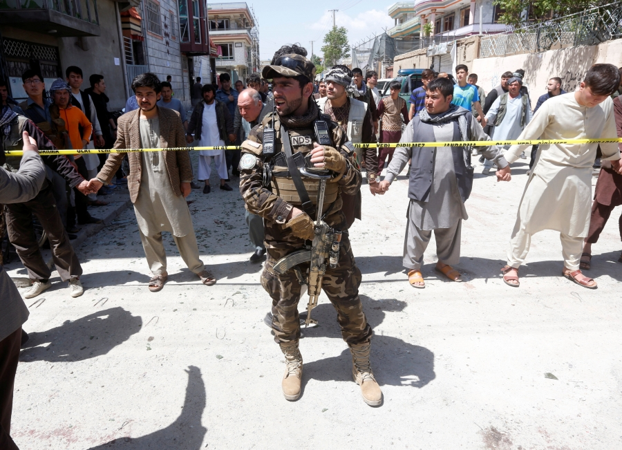 An Afghan security forces member stands guard at the site of a suicide bomb attack in Kabul.