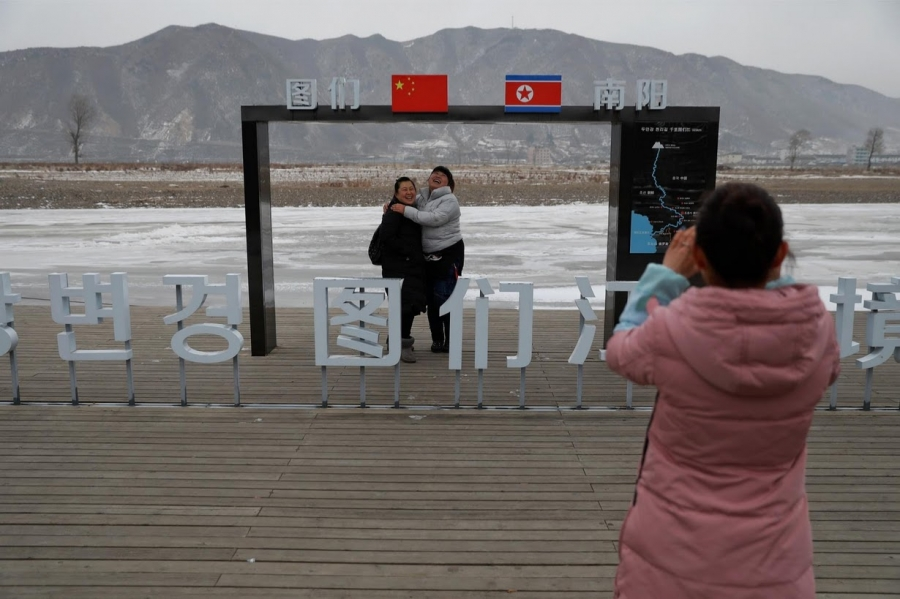 People have a picture taken of themselves with North Korea in the background, in Tumen, China.