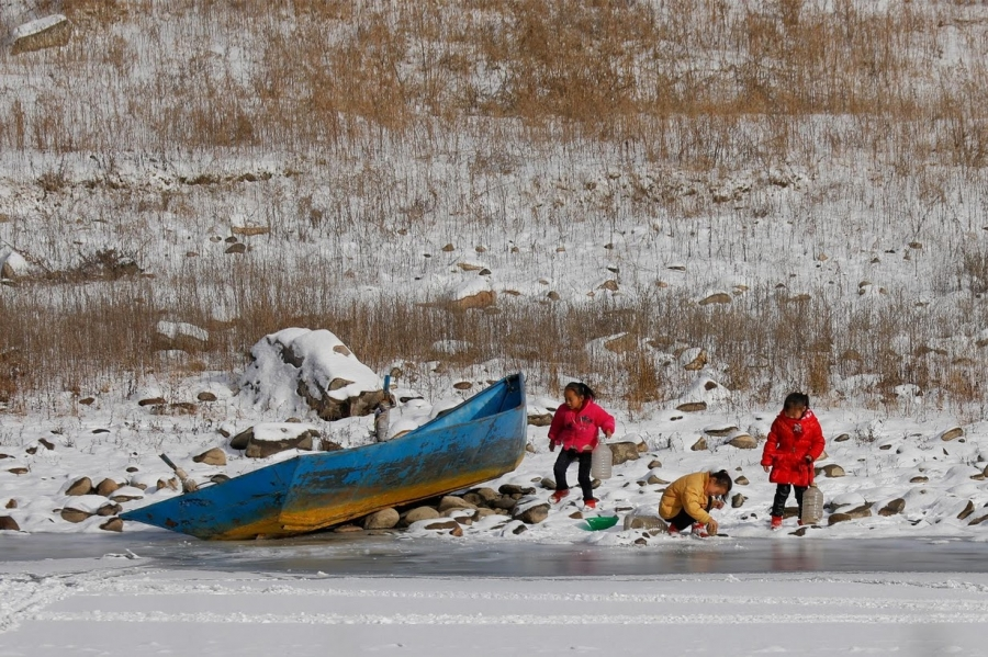 North Korean girls are photographed from the Chinese side of the border as they collect water from the frozen Yalu River near Linjiang, China.