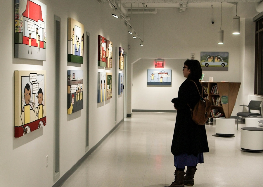 """A woman looks at the exhibit, """"Kulap: New Works by Bren Bataclan"""" at the BCNC Pao Arts Center in Boston."""