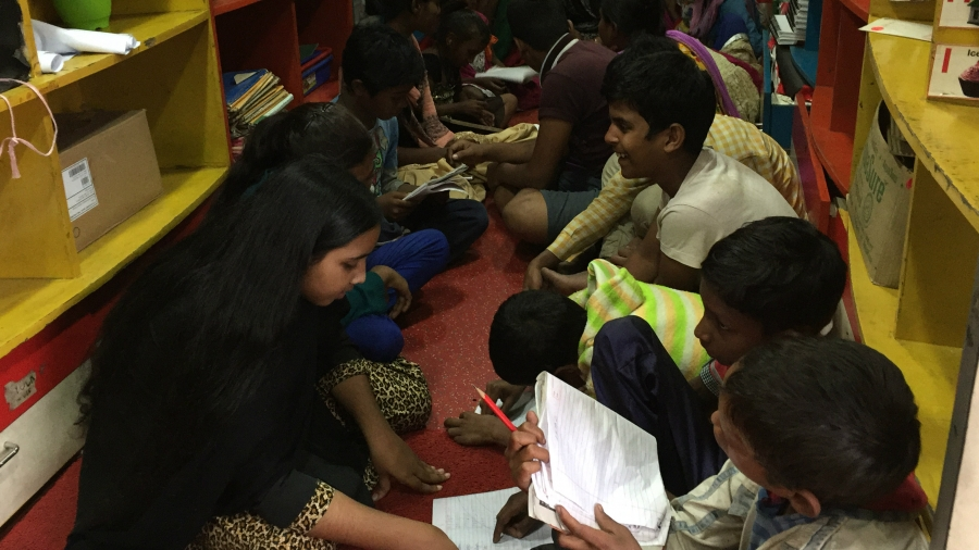 Children sit on the floor of s Save the Children mobile learning center tutoring each other.