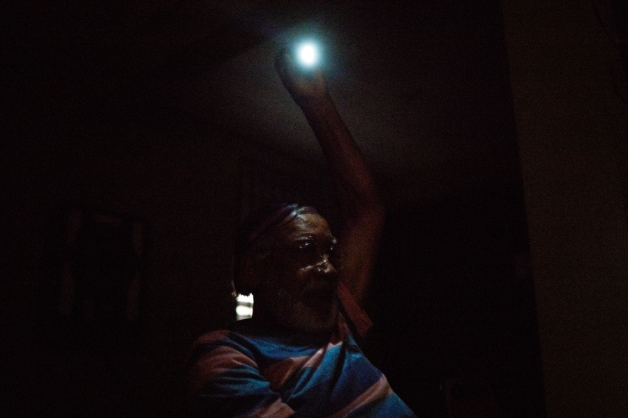 person hanging a lightbulb in a dark room