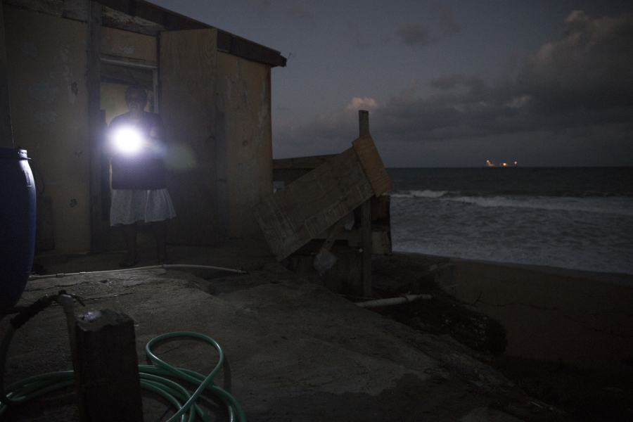 Irma Torres guides herself by flashlight at her home