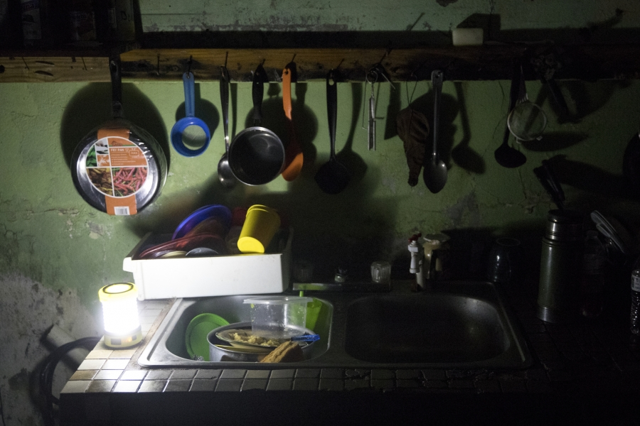 The kitchen of Irma Torres and her husband Jose Morales is lit by a battery-powered lantern