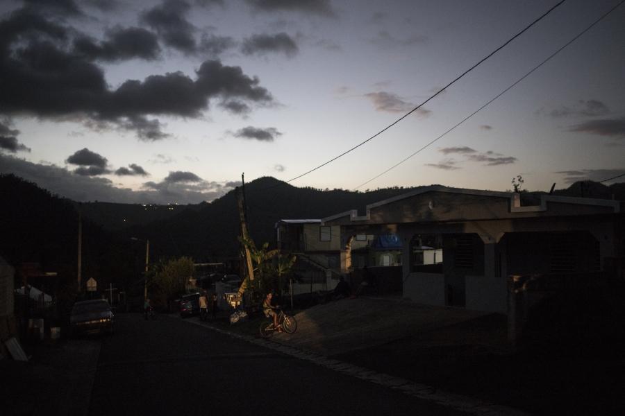 Car headlights illuminate a boy on his bike in the town of Utuado