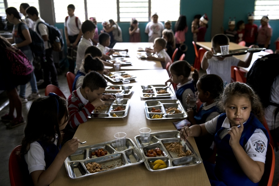 Students at the Jose R. Barreras school eat lunch in a dark cafeteria