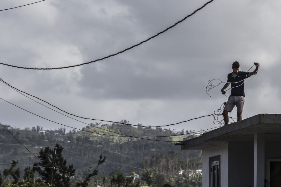 A man works on his home in Morovis, Puerto Rico, as residents in the neighborhood await for power to come back on.