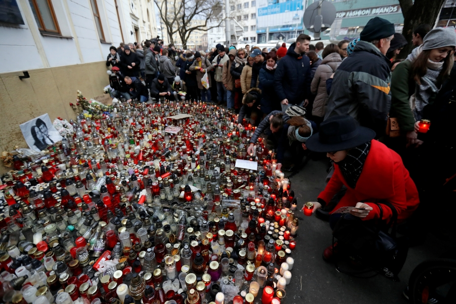 People light candles during a march in reaction to the murder of Slovak investigative reporter Jan Kuciak and his fiancee Martina Kusnirova,
